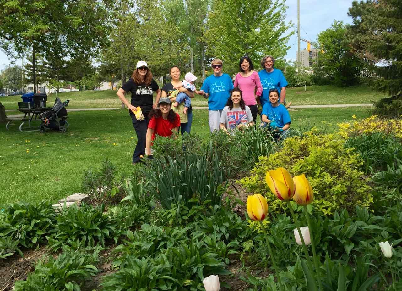 The Volunteers of the Ben Nobleman Park Community Orchard posing in front of their pollinator garden.